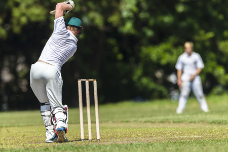 Cricket game closeup player batting ball stroke strike action high school teams. Imagens