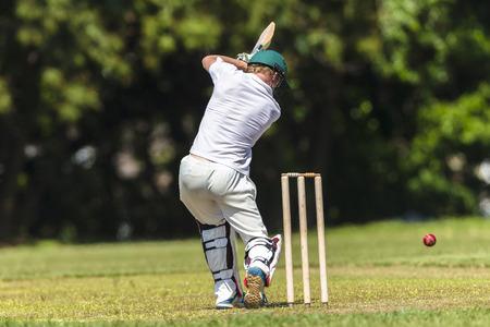 Cricket game closeup player batting ball stroke strike action high school teams. Stockfoto