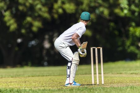 batting: Cricket game closeup player batting ready waiting ball to strike action high school teams.