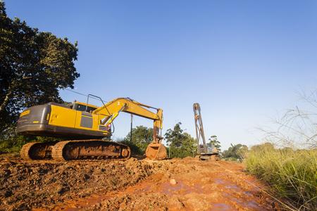 Earthworks Excavator bin and mobile crane industrial earthworks construction machines on site.