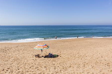 bathers: Beach blue ocean tent holiday bathers swimming coastline landscape.