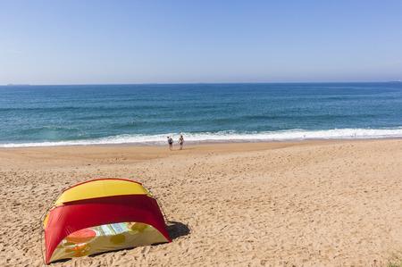 bathers: Beach sands blue ocean tent holiday bathers swimming coastline landscape.