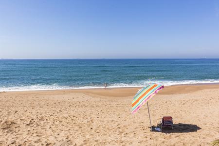 bather: Beach blue ocean water umbrella holiday bather swimming coastline landscape.