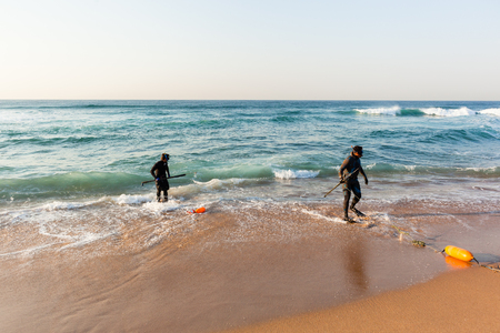 beach buoy: Divers spear fishing guns goggles line buoy  beach entry swim into ocean