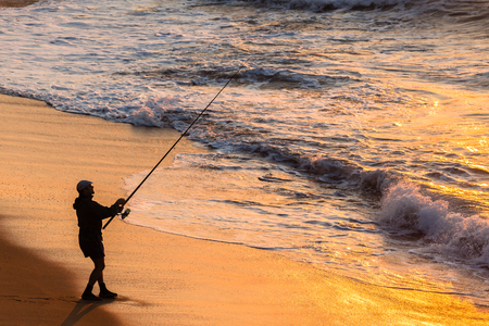 waterline: Fisherman silhouetted fishing beach waterline ocean sunrise landscape