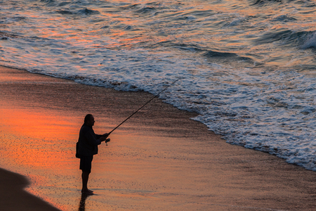 silhouetted: Fisherman silhouetted fishing beach ocean sunrise landscape
