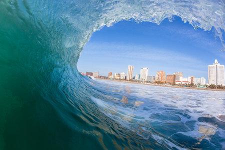 crashing: Ocean wave closeup swimming inside hollow crashing blue water.