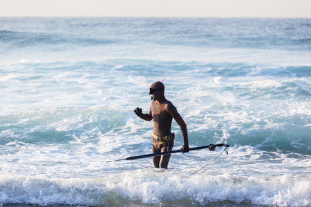 spearfishing: Diver with spear gun line buoy beach ocean swimming entry. Stock Photo