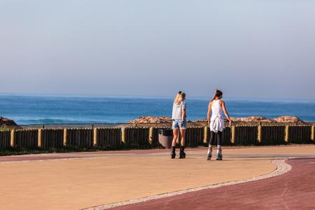 beachfront: Girls skating along beachfront promenade along ocean landscape.
