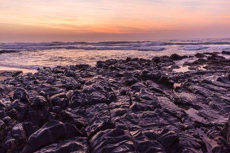 Beach ocean waves rocks coastline dawn morning landscape. Stock Photo