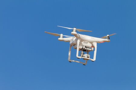 remote controlled: Drone aircraft remote controlled video camera in blue sky closeup.
