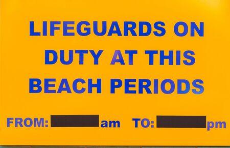a public notice: Beach lifeguard notice sign board public reading ocean swimming.