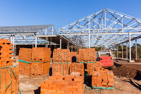 raw materials: Building construction steel roof frames with bricks blocks raw materials in mid construction
