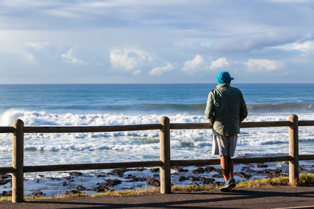 unidentified: Man unidentified surfer standing looking out over ocean waves along beach coastline .