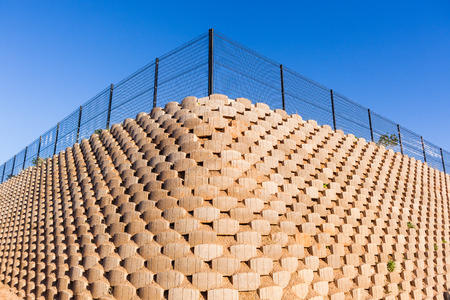 Wall retaining blocks inter locking concrete products in construction with fencing on field plateau. Stockfoto