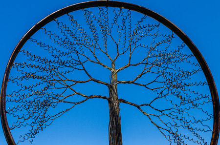Tree branches in wire art design  inside bicycle rim closeup decor against blue sky.
