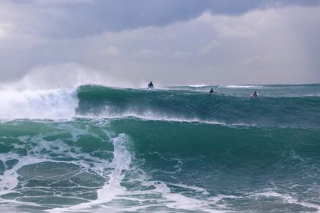 surfers: Surfers surfing escape over ocean storm large waves