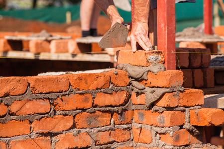 Building construction artisan hands skroll laying bricks closeup cement wire wall construction