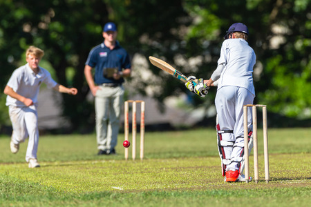 Cricket spel tieners scholen batsman bowler actiefoto.