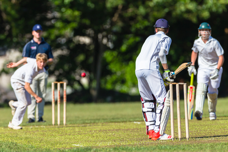 Cricket teenagers schools game batsman bowler action photo.
