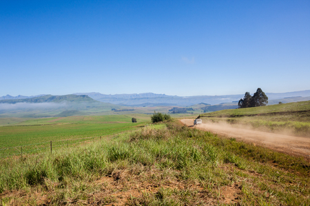 dirtroad: Vehicle travels on mountain dirt road through farming scenic landscape.