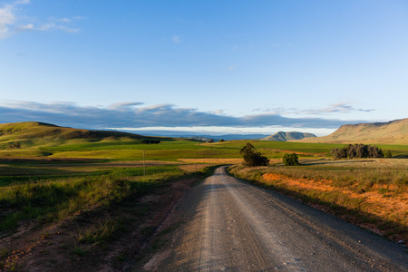 Dirt road route through scenic rural mountain farming terrain. Stock Photo