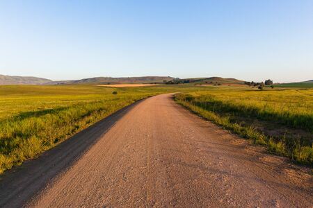 dirtroad: Mountain dirt road afternoon scenic farming landscape terrain. Stock Photo