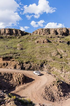 Mountains vehicle four wheel climbs dirt road up sani-pass rugged route scenic landscape