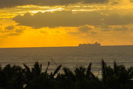 seas: Ship silhouetted crossing on ocean seas dawn morning landscape