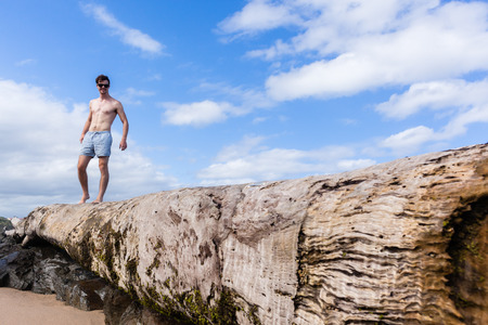 beach rain: Young man beach holidays standing on large tree trunk from rain river floods storms ocean beach. Stock Photo