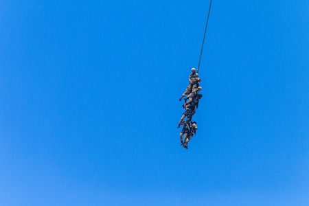 Soldiers attached to rope flying airlift below helicopter military aircraft summer blue day.