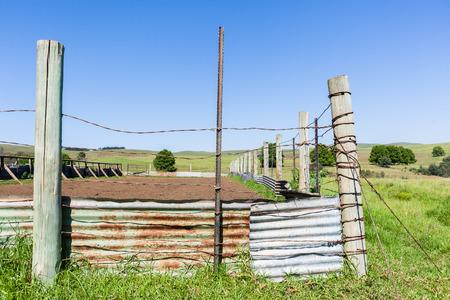 Farm rural fence wire poles cattle animal pen corral mountain landscape.