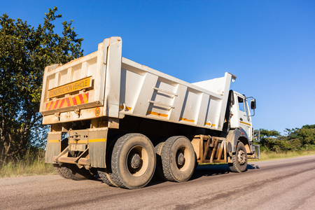 Industrial truck vehicle closeup travels countryside road towards construction site. Stockfoto