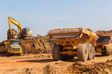 Construction industrial earthworks excavator grader machine loading earth into large truck vehicles Stock Photo