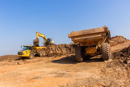 Construction industrial earthworks grader machine loading earth into large truck vehicles Stock Photo