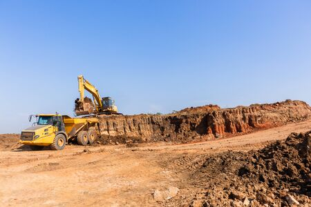 Construction industrial earthworks grader machine loading earth into large truck vehicle