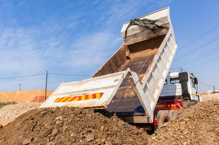 Construction Truck vehicle bucket bin tipping offloading earth closeup rear photo. Stock Photo