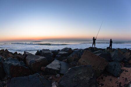 Fishing fishermen silhouetted early dawn ocean horizon sunrise beach.
