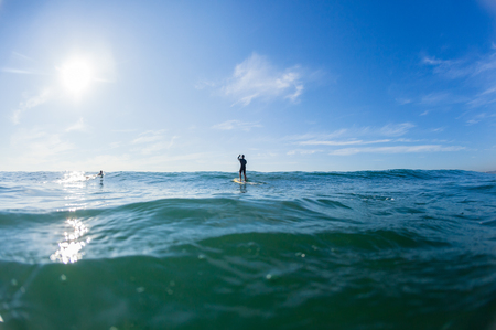 Surfer sup paddler unidentified standing on surfing board  ocean swell blue horizon rear water photo.