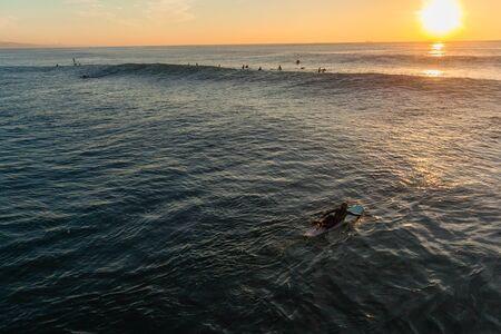 Surfer girl paddling overhead photo paddling over wave swells outside horizon ocean sunrise.