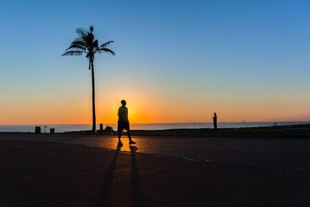 Dawn beach promenade path people silhouetted horizon ocean sunrise landscape