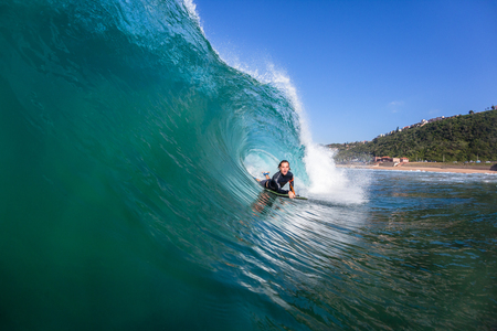 Surfer body boarder  surfing hollow wave tube ride closeup up water action photo sequence. Stock Photo