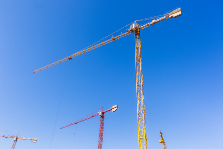 Building construction site cranes hoisting rigging machines high structures  in blue sky