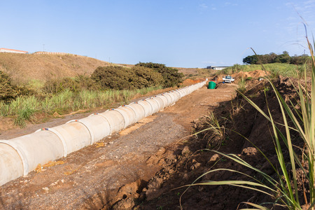 New concrete pipeline for waste water through countryside landscape vegetation. 版權商用圖片