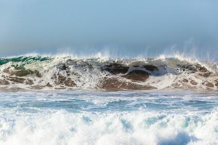 Waves upright sand water crashing ocean power closeup.