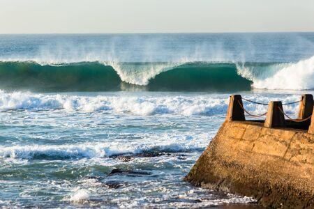 Waves crashing ocean water power front of tidal swimming pool Stock Photo