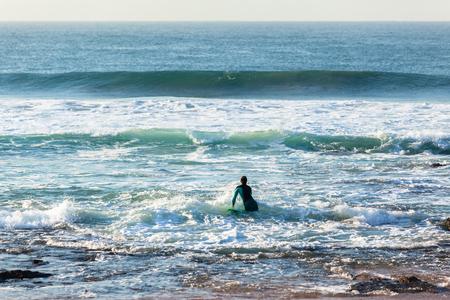 Surfer going surfing enters ocean off  beach reefs