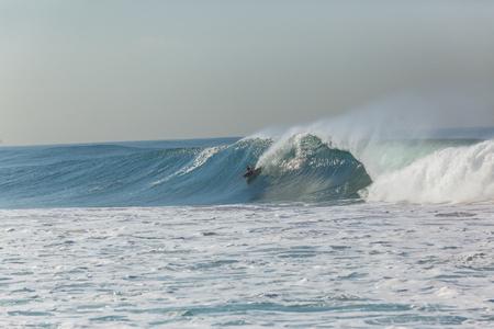 Surfer body boarder surfing rides hollow crashing ocean wave