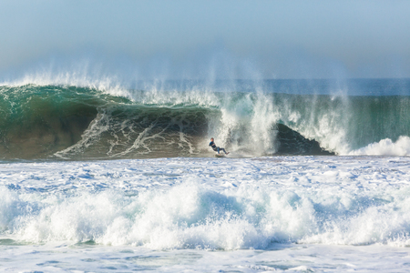 Surfer surfing tube rides hollow ocean wave .