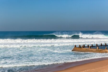 Waves crashing ocean water power towards beach tidal swimming pool.